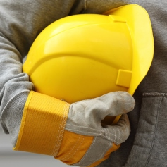 Person in work gloves holding a yellow hard hat