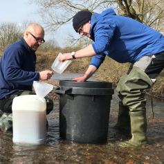 two men filtering water through plastic bins in a river